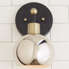 """This Young House Love Bubble Sconce has mid-century modern features. Mount it over your kitchen or bathroom sink or group them down a hallway. Available with a Dark Bronze or Nickel backplate with fun shade combinations of White, Bronze, Brushed Brass or Polished Nickel. 40 watt max, medium base socket. For even brighter lighting, try using one of our LED replacement bulbs that generate up to 100 watt equivalent brightness! Shade dimensions (5.5""""H x 6.5""""W).Backplate: 5.75"""" diameter…"""