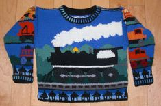This is a pattern for a sweater for a three year old boy or girl train lover. On the front a black steam engine rolls down the tracks. On the back