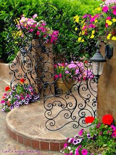 The filagree wrought iron looks marvelous with the rounded stone step and the gorgeous flowers surrounding it!