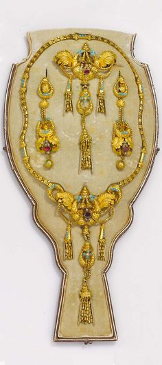 An antique suite of gold jewellery. Fitted case, yellow gold mount, original box.the first half of the 19th century