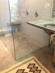 Plexi glass shower enclosure made even more raw and beautiful with the concrete floors.