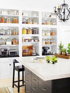 Amazing open shelving pantry storage with glass jars in kitchen.