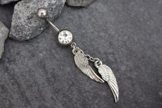 This heavenly silver angel wings dangle belly ring features a high luster clear crystal cut gem with a beautiful angel wings dangle chams. Sparkle your way into style this summer with this super cute