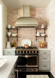 Kitchen with brick wall and La Cornue stove, designed by Jenny Wolf Interiors.