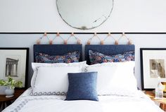 A bedroom with a French-blue wall and a headboard made out of camel leather straps and denim