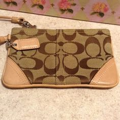 """Coach Logo Beige Wristlet with leather trim Classic """"C's canvas with leather trim in a light nude skin color. Perfect inside no marks or flaws. In pre owned condition. Coach Bags"""