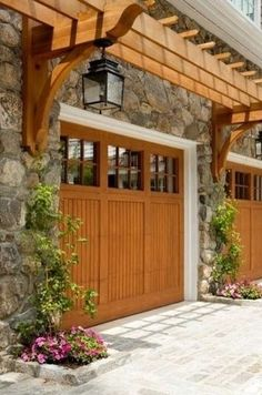 Once you've seen it you can't imagine the house without it. The matching stain on the arbor and wood carriage house garage doors contrasts nicely with stone exterior. Also think the size and shape of the light fixtures is a plus.  ~ Great pin! For Oahu architectural design visit http://ownerbuiltdesign.com
