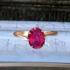 Oval ruby set in an 8-claw solitaire ring