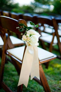 Simple and elegant aisle decor. Love the idea of tying the flowers right to the chairs.