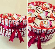 Torte aus Süßigkeiten weiße-glasur-kinderriegel-kinderjoy-überraschungseier