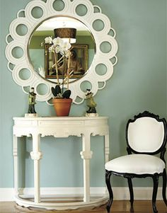 White Console:  Small elements add drama to a room. Ron Woodson and Jaime Rummerfield painted this foyer wall a serene sage green to highlight the lovely off-white Sunset mirror and an Asian-inspired console. For an extra touch of glamour, a vintage parlor chair was added.  Pictured, Sherwin-Williams's Hazel 6471.