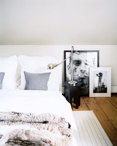 A low bed draped in luxe white bedding, a fur comforter and layered frames