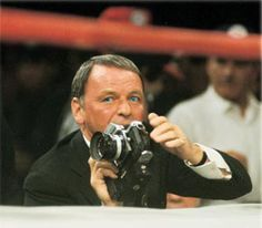 Frank Sinatra, shooting the Joe Frazier versus Muhammad Ali fight for LIFE magazine, holding his camera ringside at Madison Square Garden. New York, New York 3/8/1971