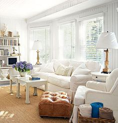 A cottage living room with all white furniture and slipcover with a sisal rug.