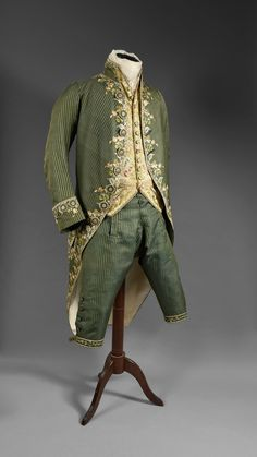 3-piece suit, France, ca 1800. Green and bronze iridescent striped silk pekin and blue embroidered, polychrome floral embroidery of tulips and garlands on the front, pocket flaps and cuffs, fabric-covered and embroidered buttons.