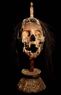IFUGAO TRIBE: HEAD HUNTING TROPHY SKULL #8  HAND CARVED WOOD BASE AND STATUE CROWN,  RATTAN, FIBER, BOAR HAIR, HUMAN BONE.  THE IFUGAO TRIBE, FROM THE PHILIPPINES, PLACE HEAD HUNTED  HUMAN TROPHY SKULLS OUTSIDE OF THEIR HUTS, AS WELL AS,   MOUNT THEM OVER THEIR HEARTHS INSIDE OF THEIR HOMES.