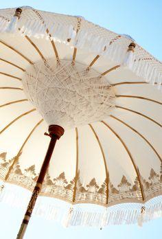 Ein Traum von Sonnenschirm, behängt mit Fransen, Goldstickerei und Windspielen.