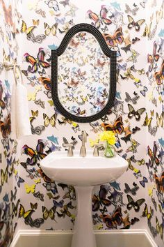 Clad in Christian Lacroix Butterfly Parade Wallpaper, this colorful contemporary powder room is fitted with a black beaded mirror mounted above a white pedestal sink finished with a satin nickel faucet.