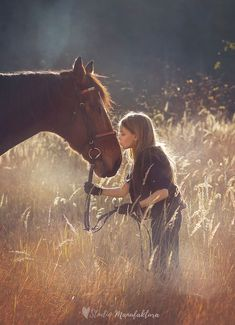Horse kiss! Girl kissing horse on nose in soft dreamy meadow.