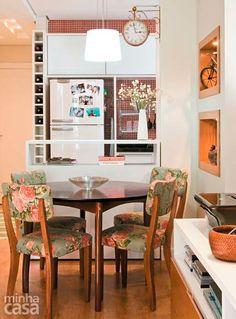 A arquiteta Cristiane Dilly escolheu para esta pequena sala de jantar cadeiras de madeira maciça estofadas com uma charmosa estampa floral. Repare no relógio de parede e também na adega que guarda vinhos no espaço ao lado da geladeira.  Foto: Minha Casa/Reprodução