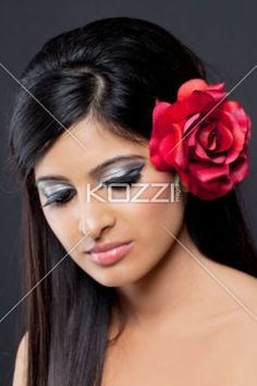 beautiful young woman with a rose in her hair. - Close-up image of a beautiful young woman with a rose in her hair, Model: Sabrina Remkissoon