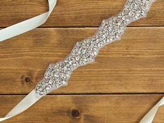 A lustrous rhinestone and pearl encrusted sash is edged with delicate beading. Finished with an ivory satin ribbon, this bridal sash secures neatly
