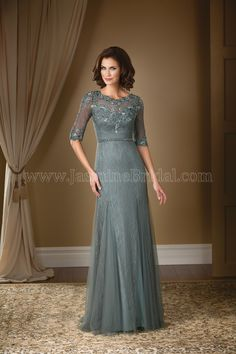 Jasmine Bridal Mother of the Bride/Groom Dress Jade Couture Style K178009 in Iron Silver Grey. Make a stylish statement at your next special occasion with this soft tulle gown. Boat neckline and A-line gown come together in this dress with lace detail throughout the dress and beaded details along the sash.