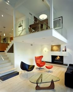 This house also uses changes in level to differentiate living, dining, and kitchen spaces in an otherwise open layout. Below is the living room; up a half-level is the kitchen; up again is the dining table. The last occupies a mezzanine that overlooks the living room and creates an intimate seating area below.