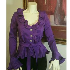 NWT Ruffled Blouse Small This fancy Ruffled Purple Blouse by Anna Kevin has pretty ruffled details around the neckline and  at the ends of each long sleeve. It has 3 silver rhinestone buttons down the front and a complimentary belt that can tie at the waist.  Cut small, Fits sizes 0-4. 97% polyester 3% Lycra Anna Kevin Tops Blouses