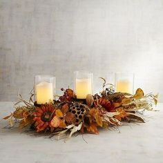 Surrounded by a rich bouquet of faux fall foliage, feathers and blooms, our candle holder adds festive elegance and warm ambience to any tablescape or shelf. Sunflower Table Centerpieces, Floral Centerpieces, Flower Arrangements, Pillar Candle Holders, Pillar Candles, Plum Art, Sunflower Wall Decor, Fall Staples, Glass Pumpkins