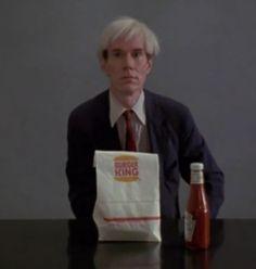 Still from video of Andy Warhol eating a hamburger.