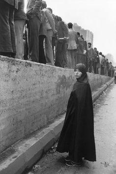 © Abbas/Magnum Photos IRAN. Tehran. December 1978. A chador clad woman stands behind a line of men during a demo against the Shah's regime.
