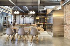 des appareils électroménagers en inox, mur de brique exposée et des suspensions ampoule dans la cuisine style industriel