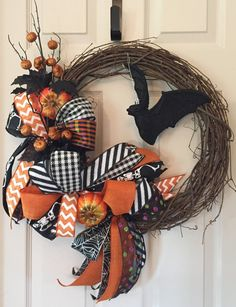 "This funky Halloween wreath is definitely a head-turner! I started with an 18"" grapevine wreath. Eight different ribbons were selected to create"