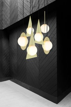Designer Tom Dixon presented a collection of pendant and table lights that combine geometric brass-plated planes with spherical glass shades in Milan last week.
