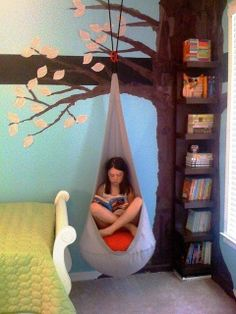 Reading nook. Tree is brown tissue paper glued to the wall w Elmer's school glue. The shelves are melamine from Ikea, sprayed brown using Krylon plastic paint. The leaves are cut from a Junie B. Jones book.