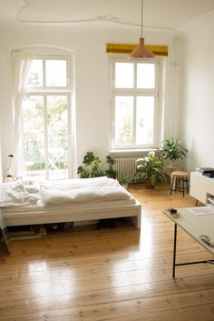 Schönes schlichtes Altbauzimmer  in Berlin mit großen Fenstern und viel Grün.