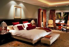 The decent bed room design with wooden bed having wooden head board .The side tables having drawers with classic table lamps . A classy sitting placed front side of bed . The flooring treated with carpet . Above raised ceiling with back light and down light .