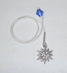 "Beautiful ""Snowflake Bay"" bookmark with a blue swarovski crystal attached to one end and a ""Snowflake"" charm attached at the other end to keep your place as you read ""Snowflake Bay""."
