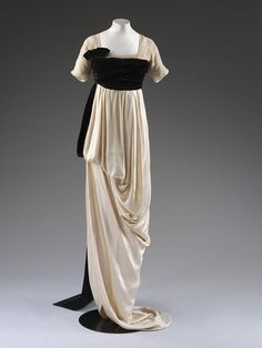 This is an evening dress made by Lucile, otherwise known as Lady Duff Gordon. This was made in London in 1913. It is made of satin and trimmed with chiffon and lace. This dress was for the evening and had a slit in the skirt to expose part of the leg; quite scandalous in London.