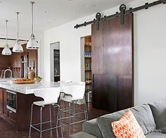 Doors are a necessity, of course, but doors also take up valuable floor space, disrupting traffic flow. A sliding door -- here, a repurposed barn door -- is an inventive remodeling solution to add cool materials and function./