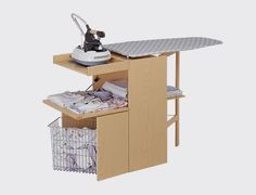 Mueble planchar Lo Stiro natural. Lo Stiro es una tabla de planchar totalmente plegable que se transforma en un mueble con mucho espacio para guardar ropa y utensilios. Con ruedas incorporadas, es de color madera natural.