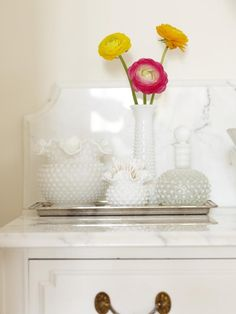 Vintage milk glass vases serve as stylish countertop storage for bathroom essentials.  Design by Sarah Richardson