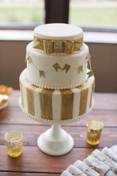 White and gold wedding cake with glitter bunting and stripes. Kate Spade inspired bow.   Cake by Izzabees Confectioneries. Photo by Kickstand Studios.
