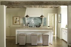 the blending of the more glam glass tile with rustic wood and light colors was done well here.