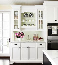 Great kitchen cabinet design with narrow glass doored upper cabinets framing open shelving