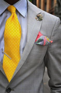 Light grey plaid jacket, white shirt with blue stripes, yellow tie with polka dots