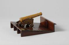 Joachim Pieter Asmus   Model van een kanon op affuit op scheepsdeel, Joachim Pieter Asmus, 1796   Model van een kanon op rolpaard op een schuin dek met boord aan de lage kant. De houten loop is 26 cm lang. Het rolpaard, voor smaller dan achter, bestaat uit twee wangen met vier trappen en een boogvormige uitsnede onderaan, die verbonden worden door het kalf, een borststuk, een dwarsbalk in het midden, de zoolplaat en een balk onder de zoolplaat, en de aslijven. De stelwig ontbreekt. De wielen…