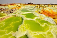 In the North East of Ethiopia lies the Danokil Desert. At its heart is a volcanic crater, Dallol, little known and seldom visited but quite extraordinary.    Surrounding the volcano are acidic hot springs, mountains of sulphur, pillars of salt, small gas geysers and pools of acid isolated by salt ridges. It makes for one of the most bizarre landscapes on planet Earth.