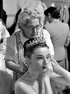 Audrey Hepburn on the set of Roman Holiday getting her necklace put on by her dresser Sally Gordon, 1952.